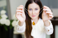 Woman keeping necklace with yellow sapphire. At jeweler's shop. Concept of wealth and luxurious life Royalty Free Stock Photography