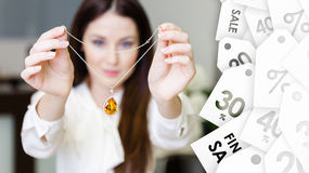 Woman keeping necklace with yellow sapphire. Special offer Royalty Free Stock Photo