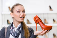 Woman keeping orange leather pump Stock Photos