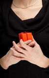 Woman keeping orange present box Royalty Free Stock Images
