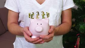 Woman keeping pink piggy bank with British pound sign concept. In room stock footage