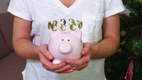 Woman keeping pink piggy bank with euros sign concept. In room stock video
