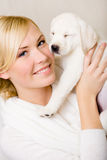 Woman keeping puppy with eyes shut near her face Stock Images