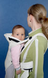The woman keeps the child in a baby sling, a side view Stock Image