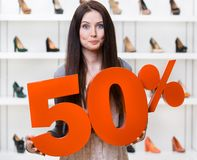 Woman keeps the model of 50% sale on footwear. Standing at the shopping center against the showcase with pumps Stock Images