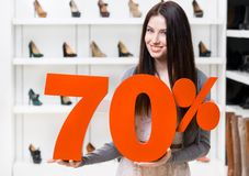Woman keeps the model of 70% sale on shoes. Standing at the shopping center against the showcase with pumps Royalty Free Stock Photo