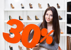 Woman keeps the model of 30% sale on shoes. Standing at the shopping center against the showcase with pumps Royalty Free Stock Photos