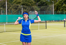 Woman keeps tennis racket on her shoulders at the  tennis court Stock Images