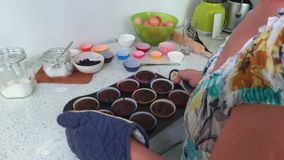 Woman keeps tray with muffins. In room stock video footage