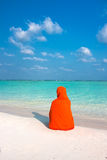 Woman with kerchief sitting on  beautiful  beach Stock Image