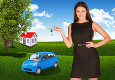 Woman with key in hand. Small automobile and house Royalty Free Stock Photo