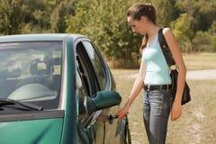 Woman with key open car door Stock Images