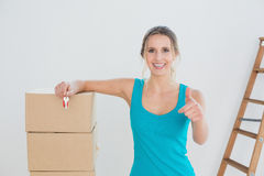 Woman with keys, boxes gesturing thumbs up in new house Royalty Free Stock Images