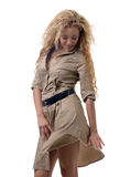 Woman in a khaki dress. Attractive blond wearing a khaki colored dress standing on white Royalty Free Stock Image