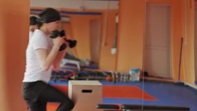 Woman kickboxer is training in a sports studio with dumbbells. 4k stock video footage
