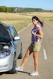 Woman kicking broken engine car wheel. Upset woman kicking car wheel after car accident or broken down engine waiting for insurance road assistance service help Stock Image
