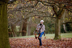 A woman kicking leaves in autumn time Royalty Free Stock Images