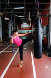 Woman kicking a punching bag. Determined sportive woman kicking a punching bag stock photos