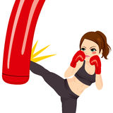 Woman Kicking Red Punching Bag. Young strong woman kicking red punching bag with powerful leg kick Stock Photography