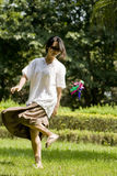 Woman kicking shuttlecock on lawn. Picture of a chinese woman kicking shuttlecock on lawn of park in a sunny autumn day Royalty Free Stock Photo