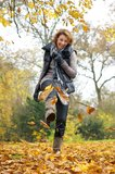 Woman Kicking Yellow Leaves in Autumn Stock Images