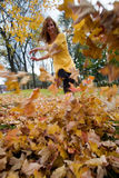 Woman kicks leaves. A redhead woman, 24, kicks through a pile of fallen autumn leaves in a park in Providence, Rhode Island, New England, USA stock images