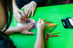 Woman and kid hands are painting circile paper with color pencil Stock Photos