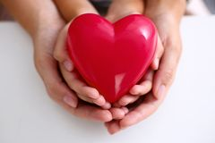 Woman and kid hold red toy heart in arms Stock Images