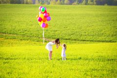 Woman with kid outside. Girl giving mother wild flowers on green royalty free stock photos