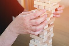 Woman and kid are playing block removing game. Trying to keep balance of tower from wooden blocks. Family leasure time. Concept of royalty free stock images