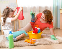 Woman and kid playing before housework. Woman and kid girl playing before housework. Mother and child daughter ready to room cleaning Stock Images