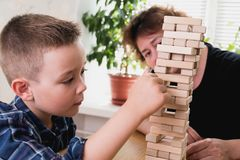 Woman and kid are playing jenga game. Trying to keep balance of tower from wooden blocks. Family leasure time. Concept Stock Photography