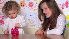 Woman with kid putting coins in piggy bank and show finger up looking at camera. Woman with lovely kid putting euro coins in piggy bank and show finger up stock footage