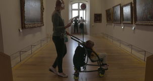 Woman and kid walking in halls of Louvre Museum