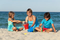 Woman and kids on the beach Stock Photos