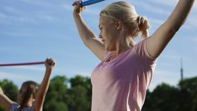 Woman with kids exercising on sports ground. Adult serious woman and children doing exercise with fitness stick on field in summer sunlight stock video