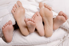 Woman and kids feet in bed Stock Photo