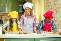 Woman and kids make pastry. Children rolling dough. Wonders in the kitchen Stock Photo