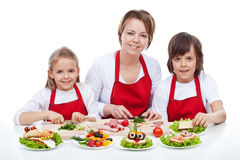 Woman and kids making creative food creature sandwiches Royalty Free Stock Images