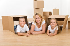 Woman with kids moving into a new home. Woman with kids playing in their new home with cardboard boxes Stock Photo