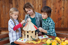 Woman with kids painting the bird house - preparing for winter. Woman with kids in autumn painting the bird house - preparing it for winter time stock image