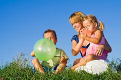Woman and kids playing with balloons Stock Images