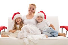 Woman with kids sitting on a sofa at christmas Royalty Free Stock Photos