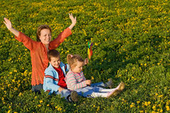 Woman with kids on the spring field. Full of dandelions stock photography