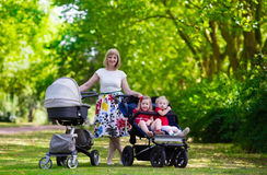 Woman with kids in stroller in a park Stock Photography