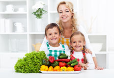 Woman and kids with vegetables in the kitchen Stock Photos