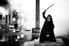 Woman killer holding Japanese sword on a post-apocalyptical landscape. Woman killer holding Japanese sword on post-apocalyptical landscape stock image