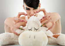 Woman killing her teddy bear Stock Photos