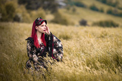 Woman in kimono on field. An alternative model with piercings and red hair wearing a kimono on a field Royalty Free Stock Photos