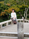 Woman in kimono in Japanese garden. Kyoto, Japan - September 30, 2015: Young girl in beautiful kimono sitting on a stone bridge in traditional Japanese garden Royalty Free Stock Images